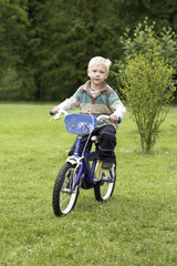 young boy bicyclist in green