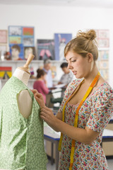Serious student sewing clothing in home economics classroom