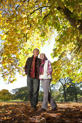Laughing senior couple walking through park beneath autumn leaves