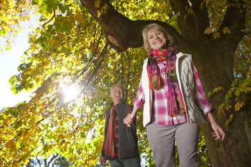 Smiling senior couple walking through park beneath autumn leaves