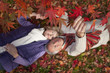 Smiling senior couple laying on ground underneath red autumn leaves
