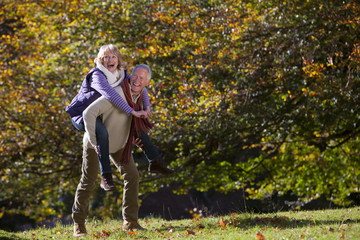 Senior man giving wife a piggyback ride in autumn park