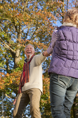 Happy senior man walking and holding hands with wife in autumn