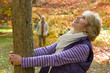 Smiling senior woman hugging tree in autumn