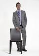 Joven ejecutivo de pie detràs de una silla.
