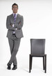 Joven ejecutivo de pie al lado de una silla.