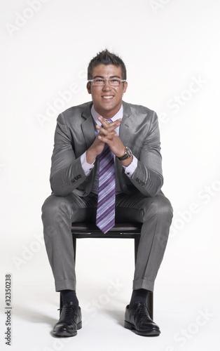 Joven ejecutivo sentado en una silla.