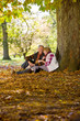 Happy senior couple sitting under tree covered in autumn leaves