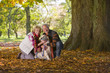 Happy senior couple sitting in autumn leaves petting dog