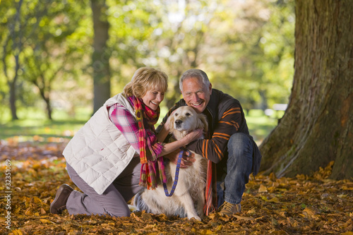 Happy senior couple sitting in autumn leaves petting dog