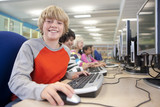 Smiling boy using computers in school computer lab