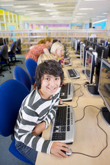 Smiling student using computers in school computer lab