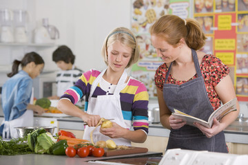 Teacher helping student with recipe in home economics class
