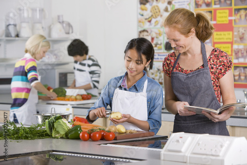 Smiling teacher helping student with recipe in home economics class