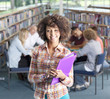 Smiling student standing in school library with study group on background