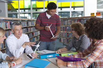 Teacher explaining wind turbine models to students in school library
