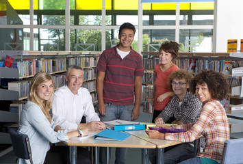 Teacher working with students in school library
