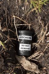 Geocache im Erdversteck mit Wurzeln