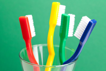 colored toothbrush in a glass on a green background