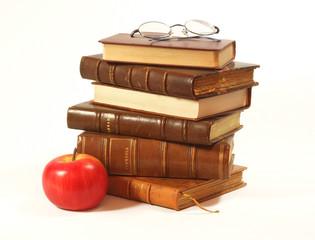 pile de livres anciens, pomme et lunettes