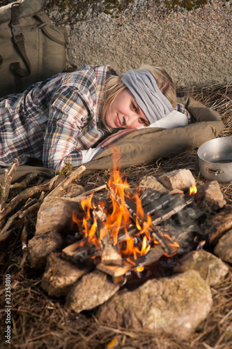 Hiking woman with backpack sleep by campfire