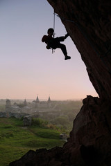 Silhouette of rock climber against old castle