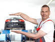 Car mechanic in a garage holding his hands over and among a car