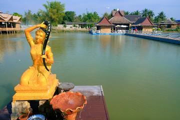Golden statue of a Buddhist deity, a pond, bridges, houses