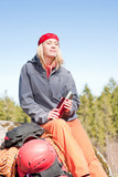 Active woman rock climbing relax with thermobottle