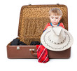 A funny boy with sombrero is in the suitcase
