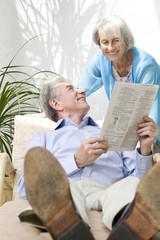 Glückliches älteres Paar liest Zeitung