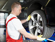 Motor mechanic is changing a summer tyre in a garage