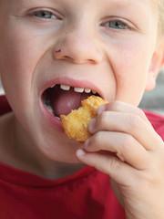 Jeune garçon mangeant un beignet de poulet (nuggets) #2