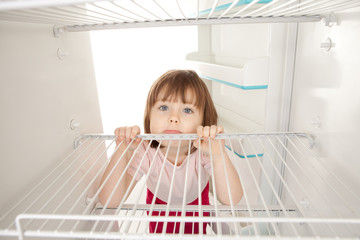 Girl looking in empty fridge