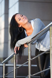 Beautiful young woman leaning on the handrail poster