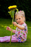 Child with a sun flower in the garden