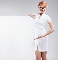 Woman wearing white coat with empty board