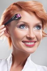 Beautiful smiling woman using dermaroller on face