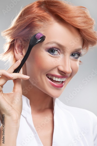 Beautiful smiling woman using dermaroller on face