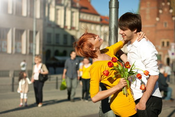 Woman holding flower bouquet smiling at man.
