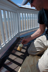 Painter Staining Oceanside Deck