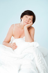 Charming thinking woman sitting on her bed