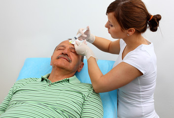 Older man receiving botox injection in his wrinkles