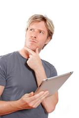 Nachdenklicher junger Mann mit Tablet PC