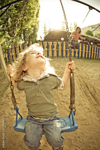 Child on swing in summer