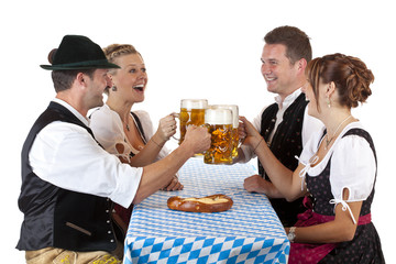 Bayrische Männer und Frauen stossen mit Oktoberfest Maß Bier an