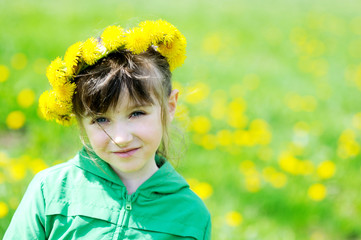 Portrait of little girl with a wreath of yellow dandelions
