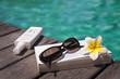 Livre, lunettes et crème solaire à la piscine