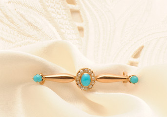 Golden brooch with turquoise and pearls on silk