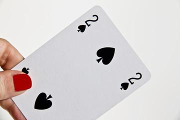 Mano di donna che tiene la carta del due di picche